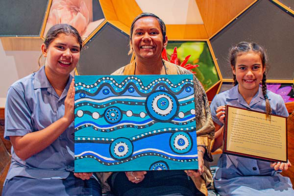 Students from St Mary's Catholic Primary School with the AJA art work. Tilly (left) and Mia (right) with Minister Selena Uibo.